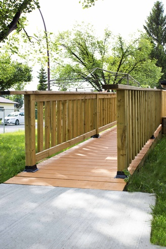 A large concrete pad leads to a gently-sloped wooden ramp.