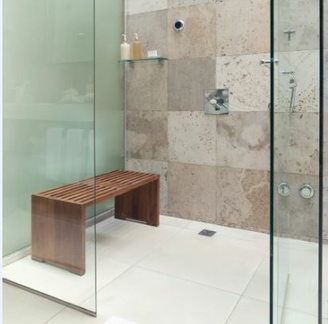 A glass shower enclosure with no change in tile surface between the inside and outside of the shower.