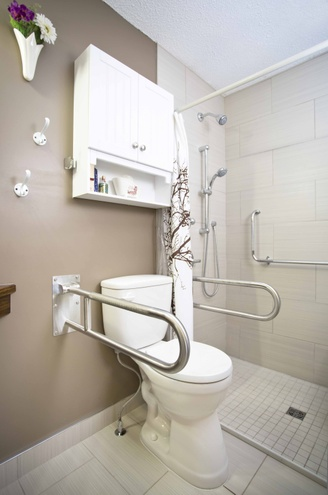 Comfort-height toilet with drop-down grab bars.