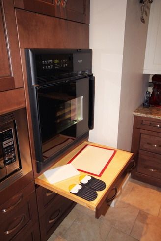 A side-opening oven in a kitchen features a pull out shelf directly under it, ready for a hot dish to be placed on it.
