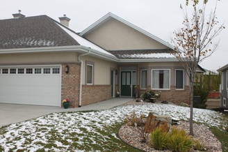 A photograph of a large suburban home features an even pathway from the driveway to the front door and a zero step entrance into the home