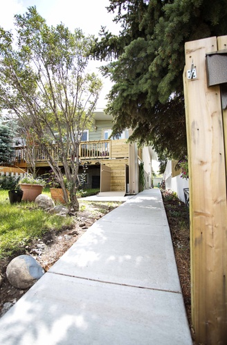 A concrete pathway leads up to a home and a porch lift.