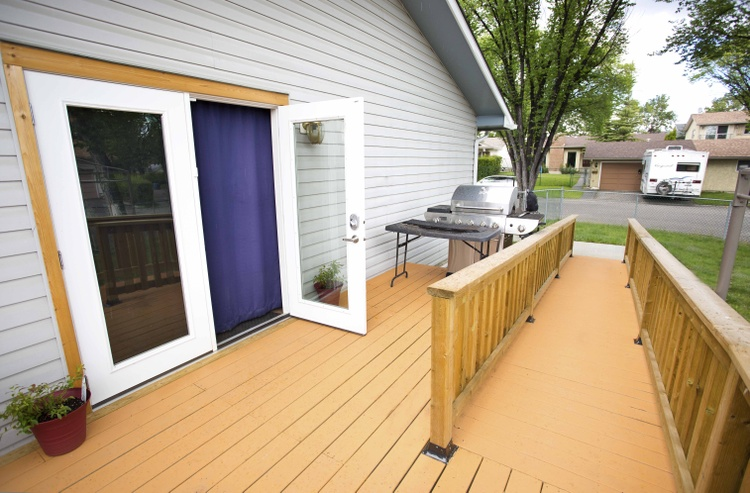 The outside of a home shows a ramp leading to a patio space with a set of double doors into the home.
