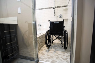 A roll-in shower enclosure with a shower wheelchair in place