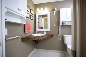 A residential bathroom shows a corner counter and sink with empty space underneath