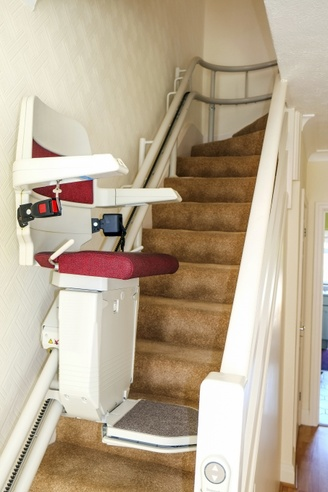 A photograph of an interior stair lift in a stairway with carpet.