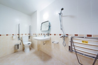 A wide-angle photograph of a wet room's toilet, sink and shower, including a showering table