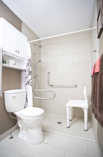 A photograph of a residential bathroom picturing the toilet and shower enclosure and a shower chair