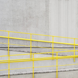 A photograph of a concrete wall with a yellow railing alongside a ramp