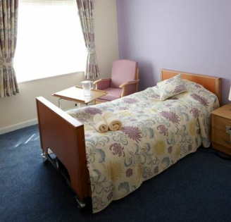 A photograph of a bedroom featuring a twin bed, night table and chair, with a purple wall and patterned bedspread.