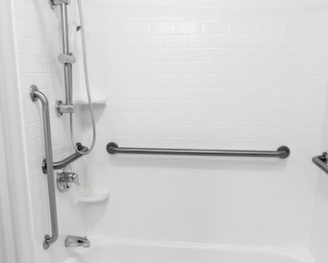 A residential shower with multiple grab bars installed.